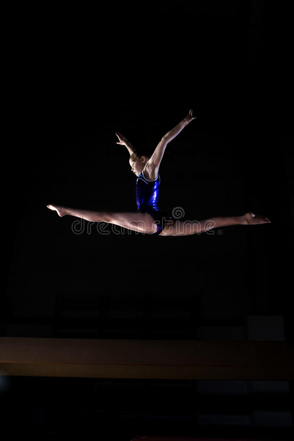 Female gymnast performing splits in air, low angle view royalty free stock photos