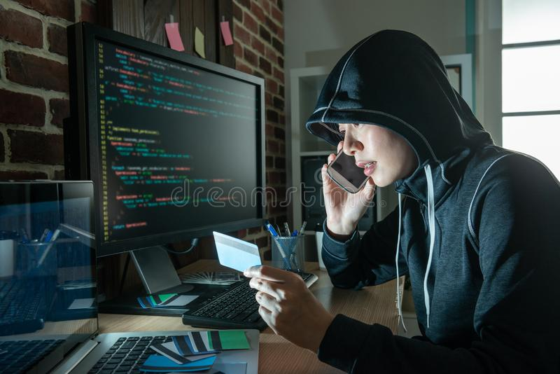Female hacker doing phone fraud and robbery. Demanding victim money thru stolen credit cards. speaking and blackmailing poor victims royalty free stock photography