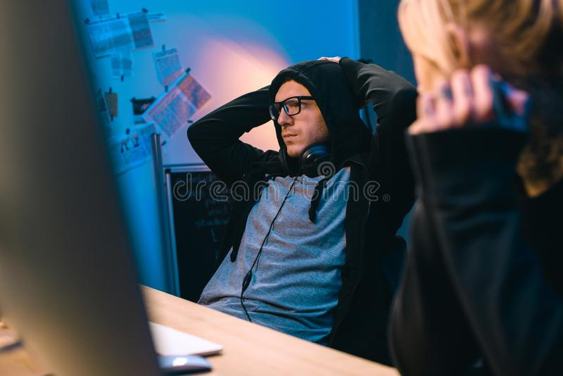 Female hacker looking at depressed accomplice. At workplace stock photography