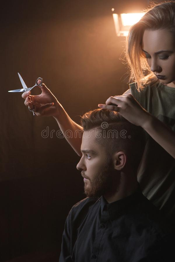 Female hairdresser cutting male hipster hair stock photography