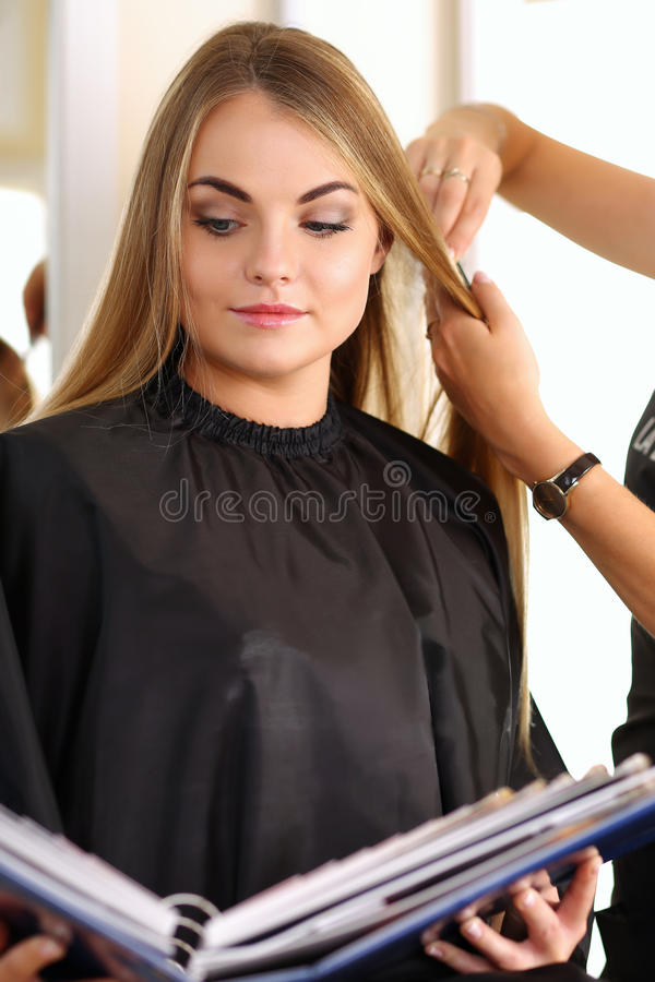 Female hairdresser hands holding comb and scissors. Making hairdo to pretty smiling blonde customer woman with sample book in hands. Hairdresser salon, barber stock photos