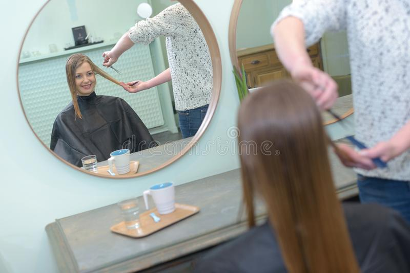 Female hairdresser making hairstyle to brunette girl royalty free stock photography