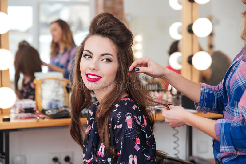 Female hairdresser making hairstyle to cute woman in beauty salon stock photography