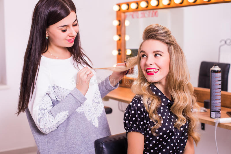Female hairdresser standing and making hairstyle to cute lovely young woman stock photo