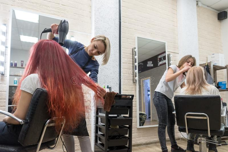 Female Hairdressers serve women clients in the hairdresser`s salon - one dries her hair, and the other paints her eyebrows. stock photos