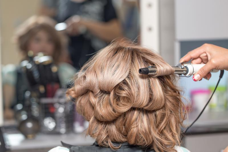 Female Hairstyles on curling in a beauty salon stock images