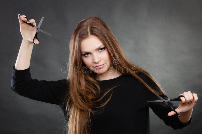 Female hairstylist barber with scissors. Style and fashion. Professional hairstylist barber with new idea of look changing. Long haired woman with scissors stock photography