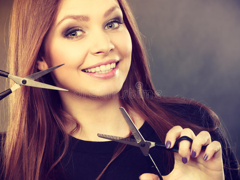 Female hairstylist barber with scissors. Style and fashion. Professional hairstylist barber with new idea of look changing. Long haired woman with scissors royalty free stock image