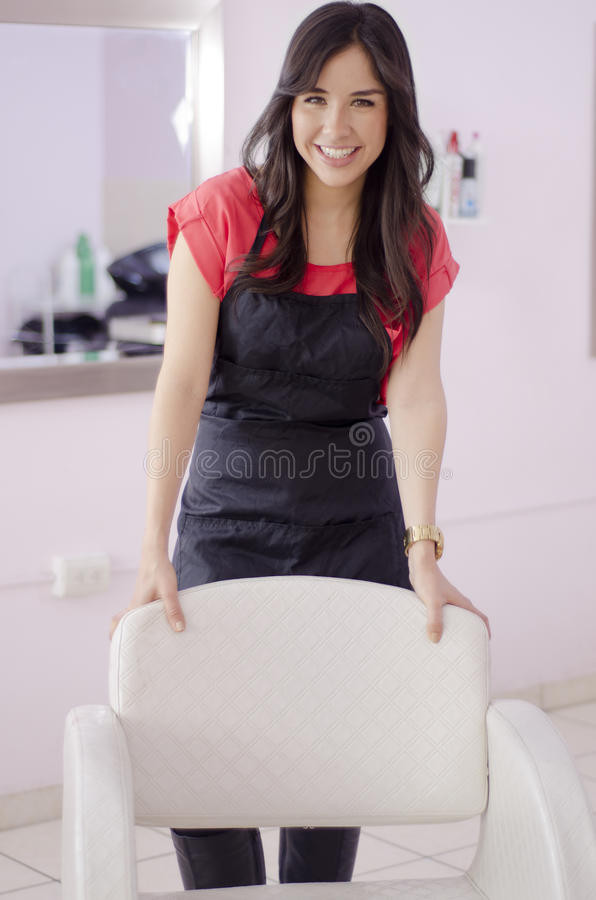 Female hairstylist greeting customers. Beautiful young hairstylist greeting customers behind a chair in a hair salon royalty free stock images