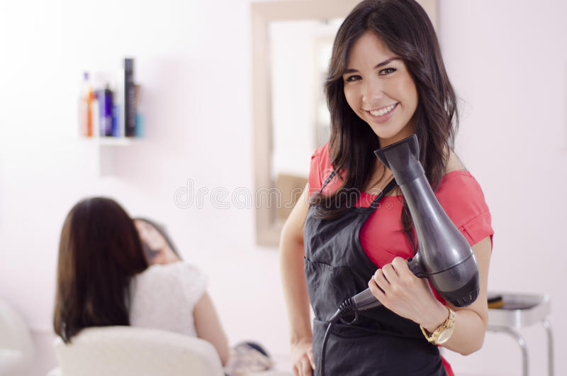 Female hairstylist working in a salon. Young beautiful hairstylist smiling and posing with a blow dryer in her hand stock photography