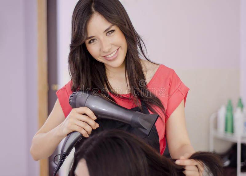Female hairstylist working in a salon. Cute female hairstylist smiling and blowing the hair of a customer in a salon royalty free stock photography
