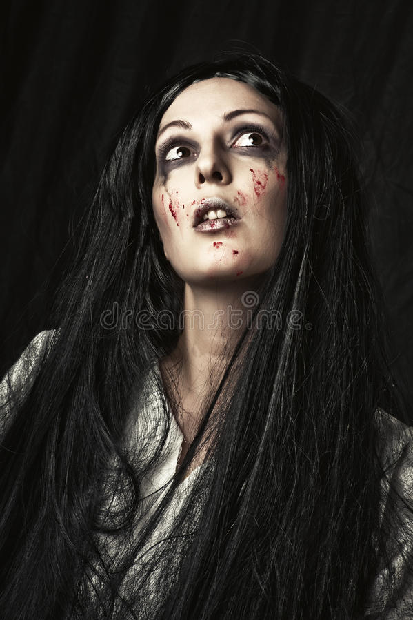 Female halloween zombie. Portrait of woman with make up for halloween - a gory bloody and scary zombie royalty free stock image