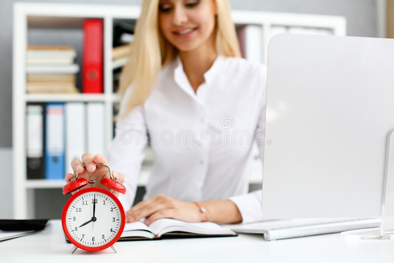 Female hand on the alarm clock a red color stands in royalty free stock photography