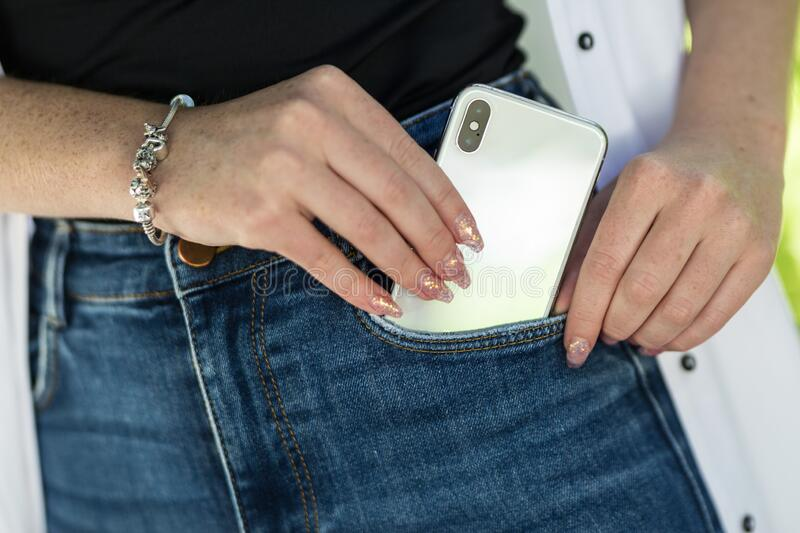 Female hand with beautiful bright design of manicure nails putting modern smart phone in blue jeans pocket stock photography