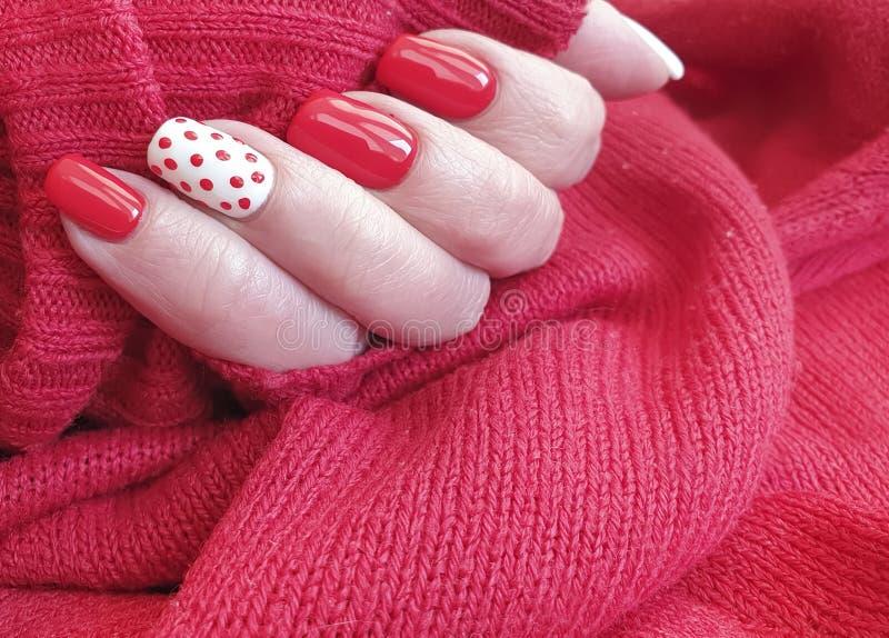 Female hand beautiful  design stylish red manicure decoration sweater elegant. Female hand beautiful red manicure sweater elegant autumn decoration design royalty free stock images