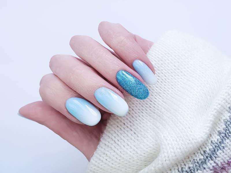 Female hand beautiful fashion design stylish ombre acrylic manicure, sweater, winter. Female hand beautiful fashion manicure acrylic blue sweater, winter ombre stock photography