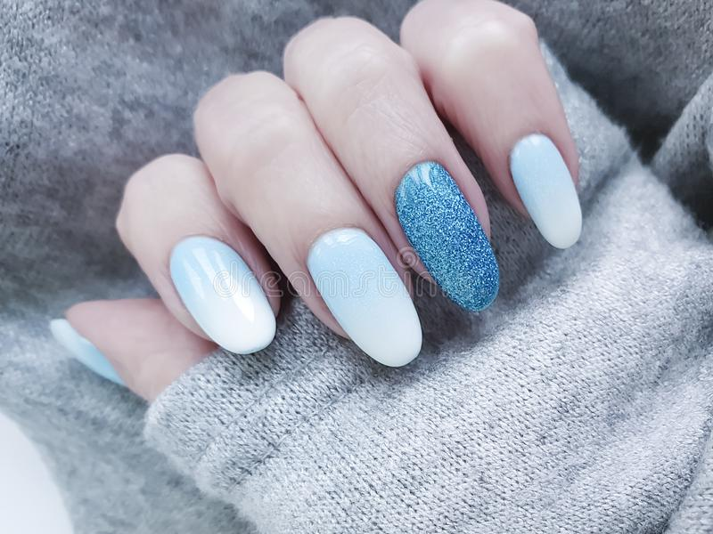 Female hand beautiful fashion blue design stylish ombre acrylic manicure, sweater, winter stock photos