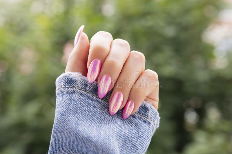 Female hand with a beautiful pink manicure. royalty free stock images