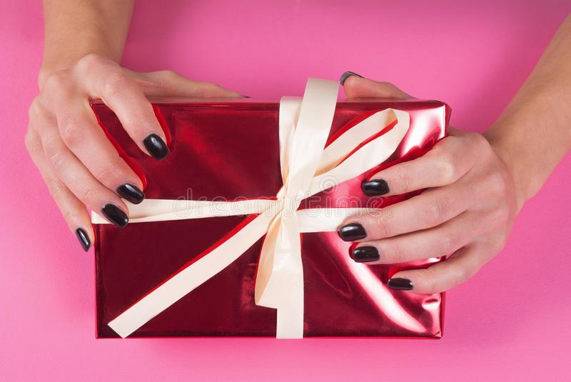 Female hand with black nails manicure on red gift box with white bow on pink background, close up royalty free stock photos