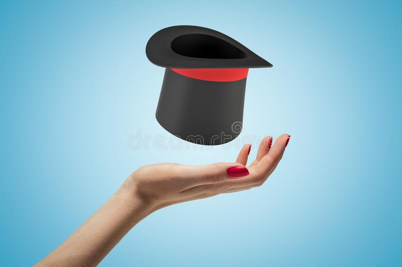Female hand with black top hat above on blue background royalty free stock photo