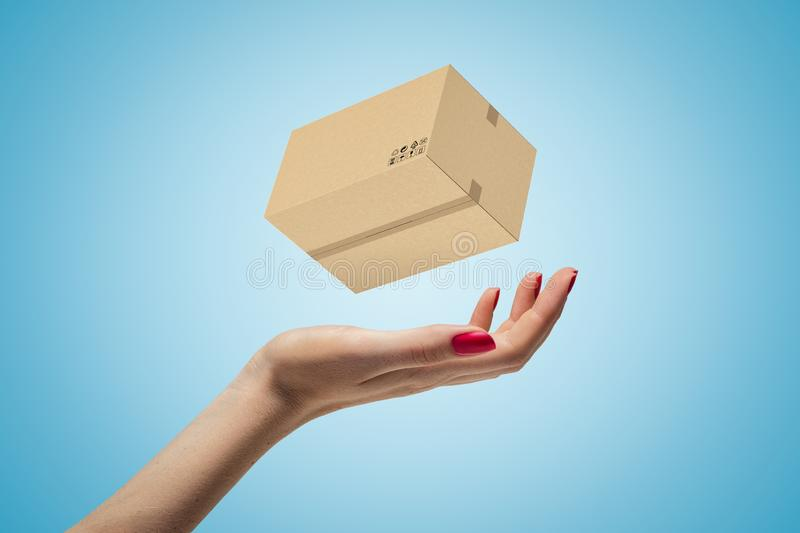 Female hand with cardboard box on blue background royalty free stock photo