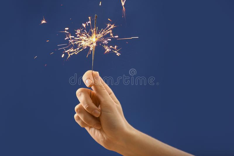 Female hand with Christmas sparkler on color background stock photos