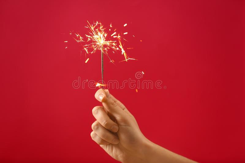 Female hand with Christmas sparkler on color background stock image