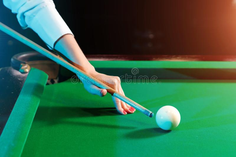 Female hand close-up, billiards, player preparing to hit the ball. Pleasant pastime, entertainment, leisure, family holidays, stock image