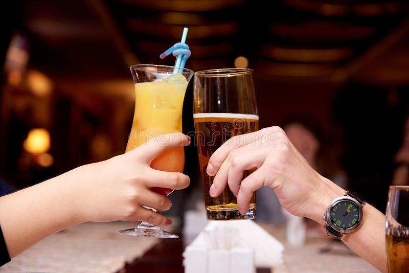 Female hand with a cocktail and male hand with beer stock images