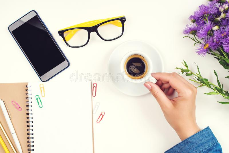Female hand with coffee cup. Top view of work desk. Coffee, glasses, notebook, pencil, glasses, paper clips and mobile phone on wh royalty free stock image