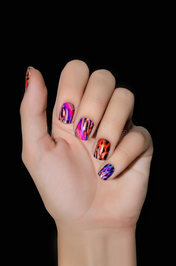 Female hand with color nail art stickers on black background royalty free stock image