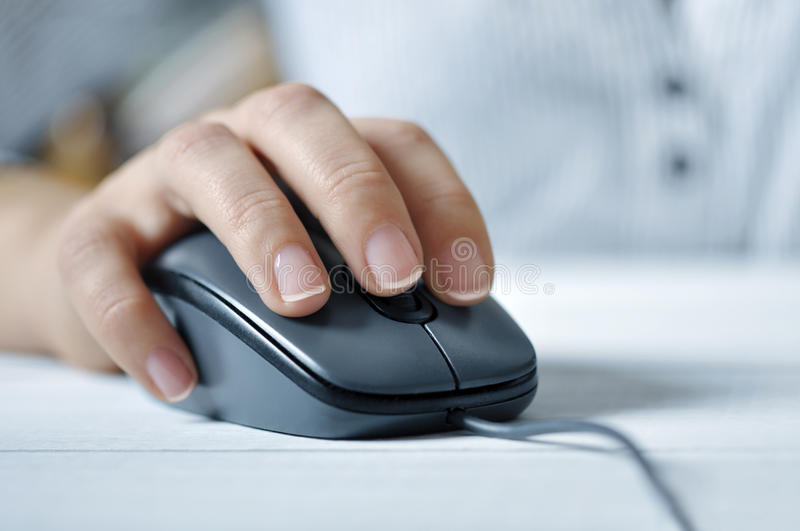 Female hand with computer mouse. Female hand clicking computer mouse closeup. Small shallow DOF royalty free stock photos
