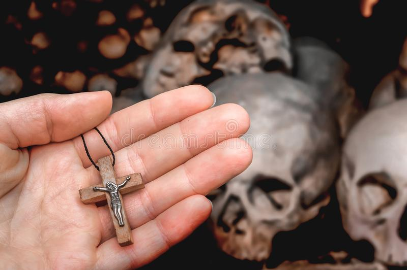 Female hand with cross on skulls and bones background. Female hand with wooden cross on skulls and bones background - religion concept stock photo