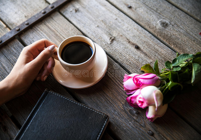 Female hand with a cup of coffee, book and flowers on wooden background. Flowers, break, work stock photo
