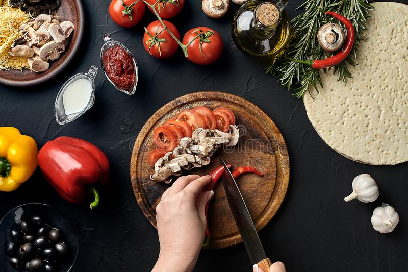 Female hand cut chilli, mushrooms and tomatoes on wooden board on kitchen table, around lie ingredients for pizza stock photos