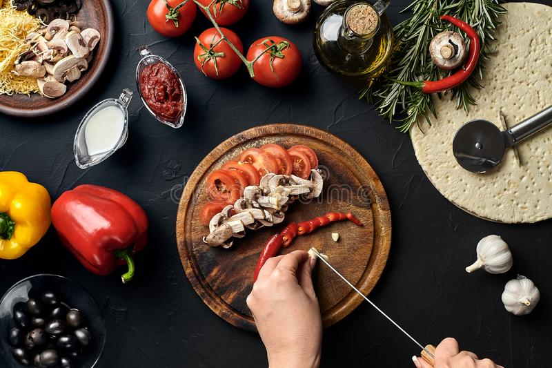 Female hand cut garlic, chilli, mushrooms and tomatoes on wooden board on kitchen table, around lie ingredients for stock images