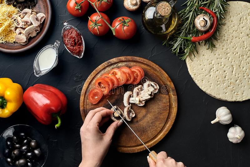 Female hand cut mushrooms and tomatoes on wooden board on kitchen table, around lie ingredients for pizza: vegetables royalty free stock photos