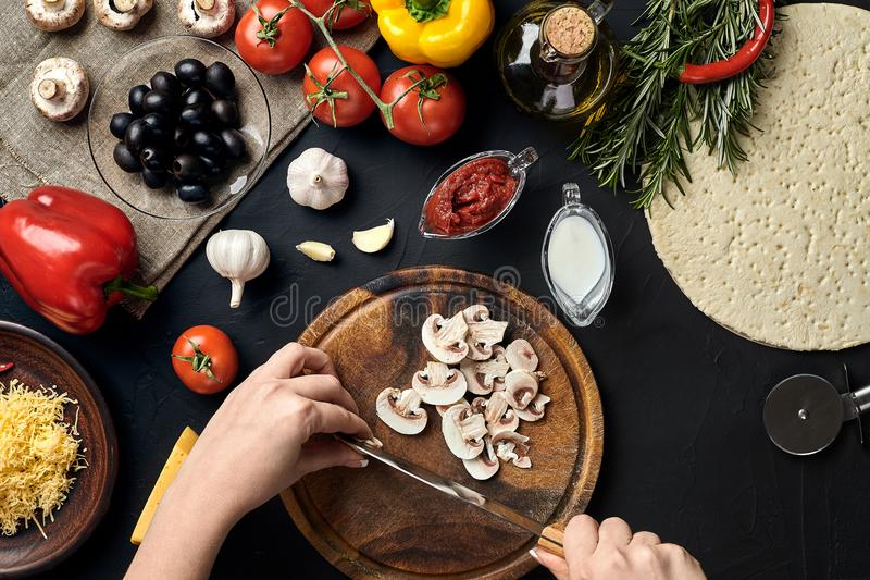 Female hand cut mushrooms on wooden board on kitchen table, around lie ingredients for pizza: vegetables, cheese and stock photography