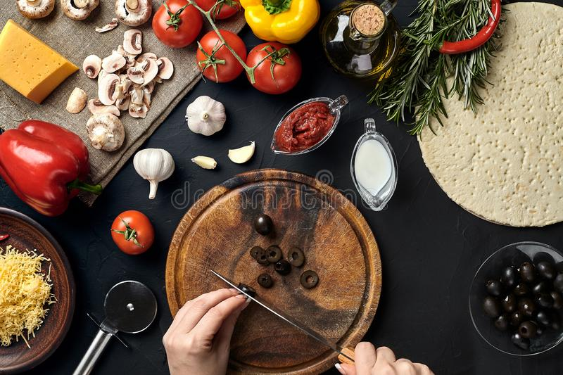 Female hand cut olives on wooden board on kitchen table, around lie ingredients for pizza: vegetables, cheese and spices. Healthy foods, cooking and vegetarian royalty free stock photography