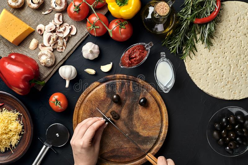 Female hand cut olives on wooden board on kitchen table, around lie ingredients for pizza: vegetables, cheese and spices. Healthy foods, cooking and vegetarian stock images