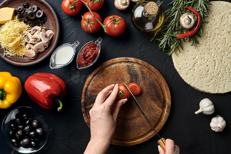 Female hand cut tomatoes on wooden board on kitchen table, around lie ingredients for pizza: vegetables, cheese and stock photos