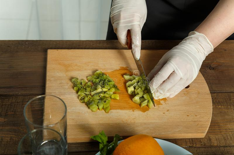 A female hand cuts a knife on a wooden kiwi plate into pieces. stock photo