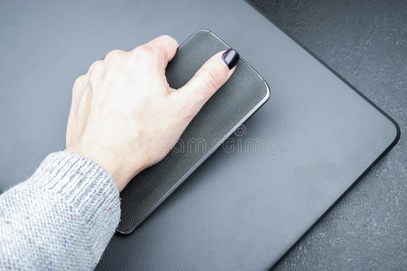 Female hand with dark nails holds a mobile phone with a knitted nylon back, which lies on a closed textured gray laptop cover.  royalty free stock image