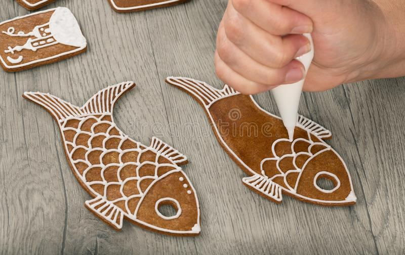 Female hand decorating baked gingerbreads in fish shape stock photography