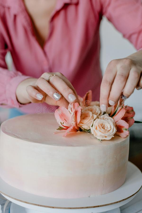 Female hand decorating pink flower wedding birthday cake on stand. Close up pastry chef decoration delicious dessert dish. Process, woman, homemade, closeup royalty free stock photo
