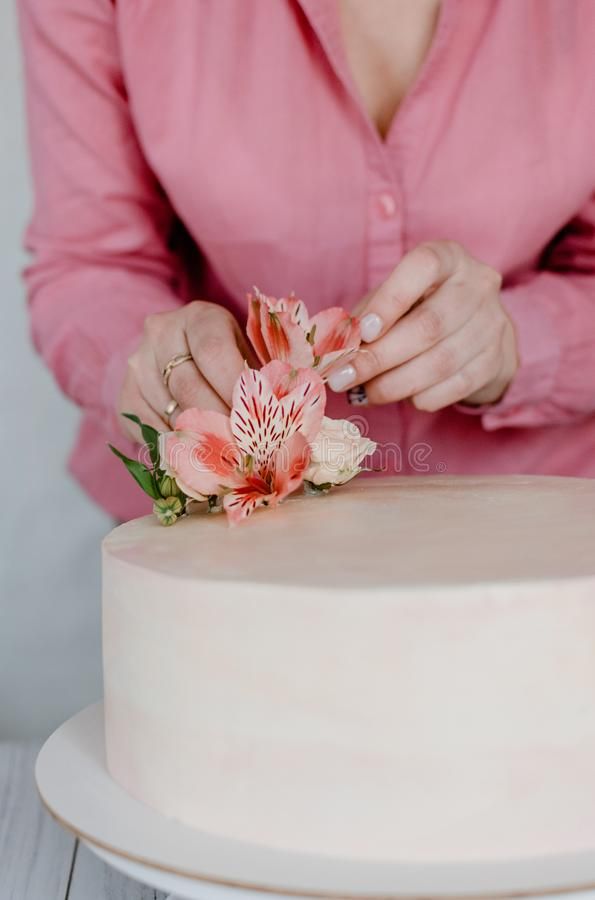 Female hand decorating pink flower wedding birthday cake on stand. Close up pastry chef decoration delicious dessert dish. Process, woman, homemade, closeup stock photo