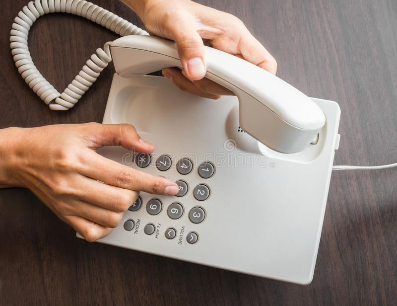 Female hand dialling out on a telephone on keypad royalty free stock image