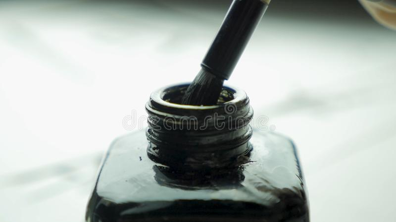 Female hand dunks brush in a jar of ink for drawing close up. Chinese Old-fashioned Paint Brushes with Selective Focus. Detail of a chinese brush while drawing royalty free stock images