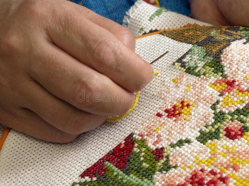 Female hand embroider at cross. Hobby and interesting working stock photos