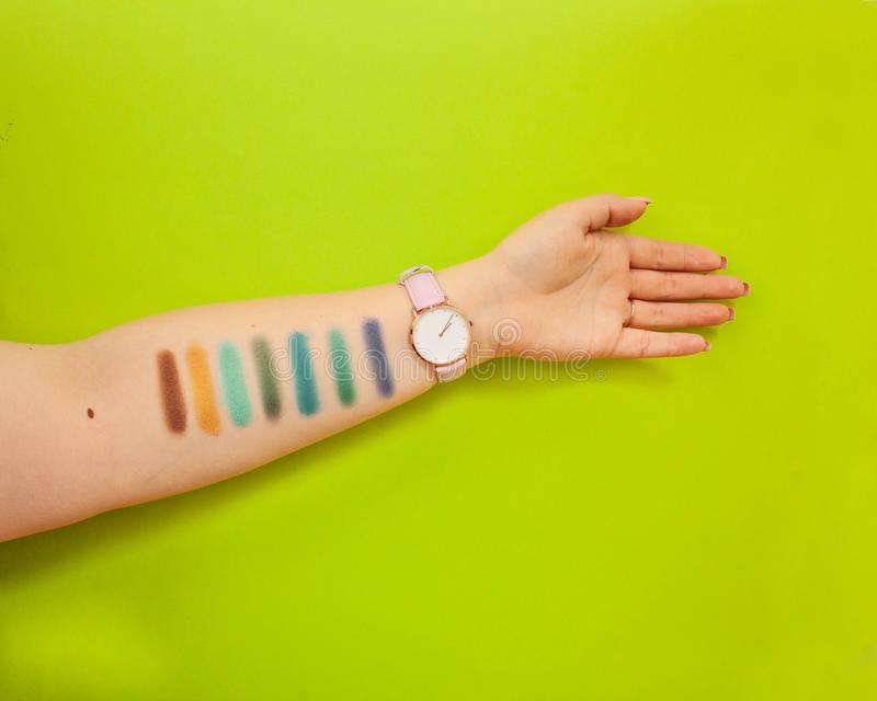Female hand with eyeshadow colors. Closeup of woman makeup artist testing different eyeshadows, showing swatches stock photo